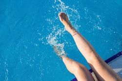 cropped young european woman kicks in the pool splashes water. Concept, carefree, summer, vacation. Copy space. View from above