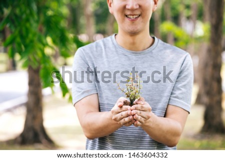 Cropped young happy Asian male volunteer with smile holding a small little tree ready to be potting in the soil. Sustainability, Save the Earth and sustain living development concept #1463604332