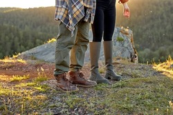 cropped young traveler tourists hiker close-up shoes boots and hiking. man and woman tourist hikers walking in mountains, forest steps trail. ravel concept. at sunset in nature