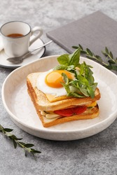 Croque madame - hot sandwich with ham, melted cheese and fried egg over gray concrete background and cup of espresso coffee. Side view, close up. Healthy delicious breakfast. Dish of French cuisine