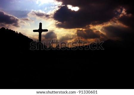 cross and god rays on the cloudy sky