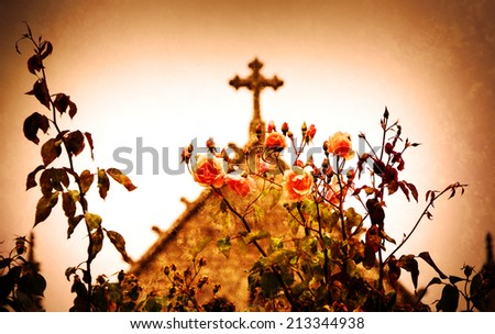 Cross and roses. A church in Dinan (Brittany, France). Selective focus on the flowers. Retro aged photo with scratches.  #213344938