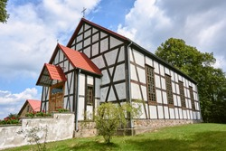 Cross and Wattle and daub country church in Poland