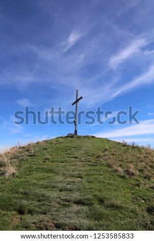 Cross at the peak of Mount Setzberg against blue sky #1253585833