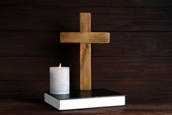 Cross, Bible and burning candle on wooden background. Christian religion