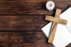 Cross, Bible and burning candle on wooden background, flat lay with space for text. Christian religion