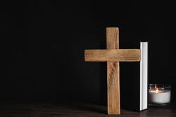 Cross, Bible and burning candle on wooden table, space for text. Christian religion
