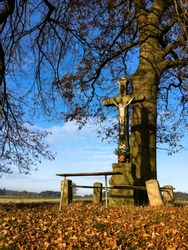 Cross by the road for travellers with a kneeling bench and a large tree in the background in the Czech Republic
