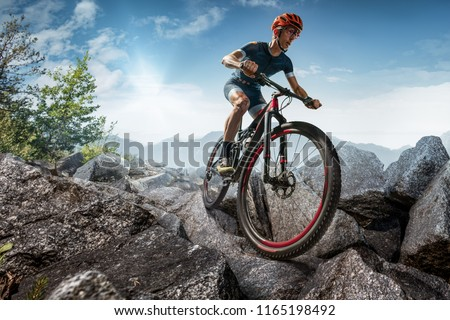 Cross-Country biker on stone trail. Male cyclist rides the rock #1165198492
