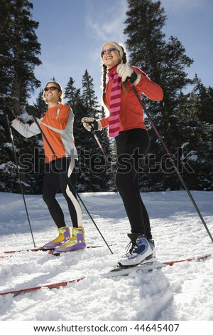 Cross country skiers smiling as they move through the snow. Vertical shot.