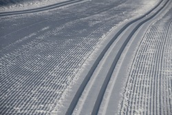 cross country skiing grooming lines in snow for nordic skate skiing or classic trails in snow made by groomers freshly groomed trail in winter outdoor sport  horizontal format leading lines type space