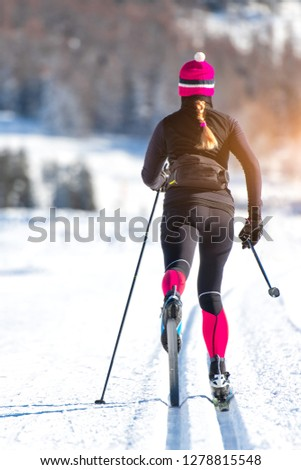 Cross-country skiing of a young athlete girl. Classical alternating technique. #1278815548