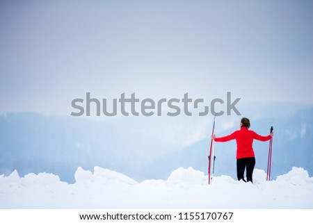 Cross-country skiing: young woman cross-country skiing on a  winter day (motion blurred image) #1155170767