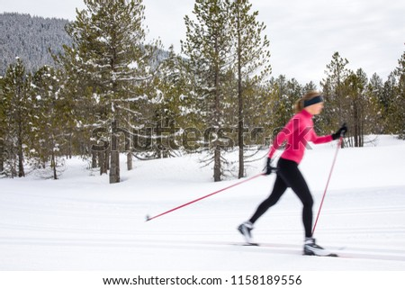 Cross-country skiing: young woman cross-country skiing on a winter day (motion blurred image) #1158189556