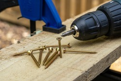 cross head countersunk brass single thread wood screws on a wooden board plank with an electric drill screwdriver and clamp outside
