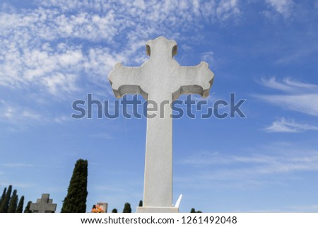 Cross in cementery with clouds, Madrid, Spain.