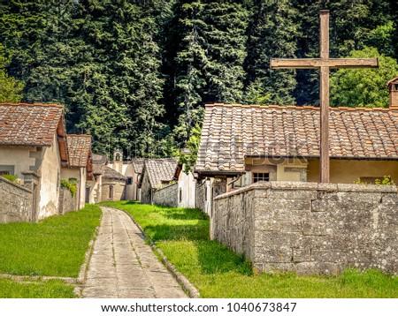 Cross in monastery settlement. Stone houses and walls in monastery courtyard. Christian cross. Camaldoli monastery, Italy.