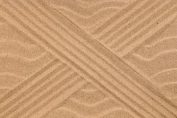 Cross lines and wavy sand lines. Texture of sand. Copy space. Top view