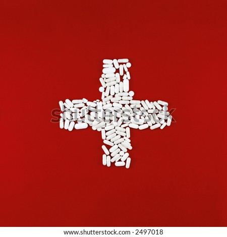 cross made of white pills on a red chalk background