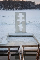 Cross near ice bath. Winter Baptism in Minsk Belarus. Baptismal bathing - a folk tradition that exists in Russia, Belarus, Ukraine. Bathing in the ice hole. Plunge into the ice water.