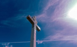Cross of Lorraine - is a heraldic two-barred cross. The Cross of Lorraine is an emblem of Lorraine in eastern France. Patriarchal cross. Sunlight, clouds.