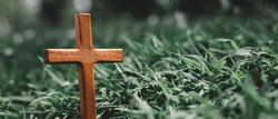 cross on a small grave surrounded by grass hill. marker standing alone. Crucifixion Of Jesus Christ. Religion concept.
