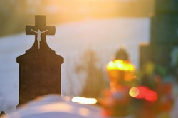 Cross on cemetery - funeral concept photo with candle and warm sunset light