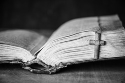 Cross on the Bible on a wooden background. Holy book. Black and white photography