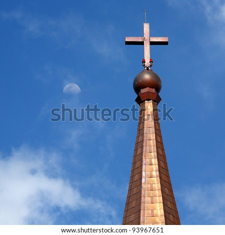 Cross on the Temple Catholic with the half circle of the moon behind Thailand