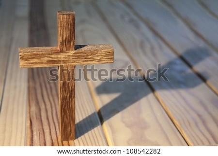 cross on wood table background - stock photo