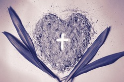 Cross or crucifix in heart shaped ash with palm leaves. Purple, monochromatic. Lent Season, Holy Week, Palm Sunday and Good Friday concept.