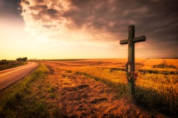 Cross over the field and dark sky during sunset