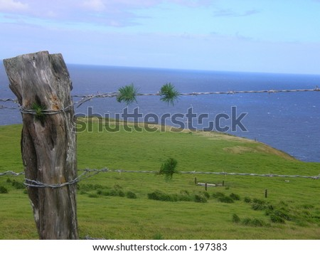 cross overlooking ocean threw a wire fence with old fence post