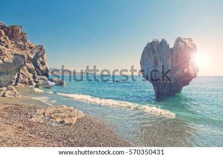 cross-processed image of huge heart shaped rock on pebble beach of Preveli with sun shining behind the rock, Crete, Greece