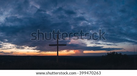 Cross (Religious Equipment) on background of beautiful dramatic sky at sunset. Dramatic sky before storm. Cross and oddly shaped cloud in the sky. Cloud like a whirlwind or mushroom. Stock photo ©