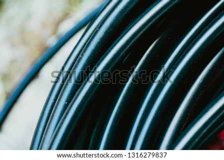 Cross sectional of HDPE pipe.The black pipe with red strip of water pipe was cut and place on the pile for plantation and Sprinkler system. #1316279837