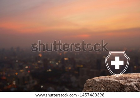 Cross shape with shield flat icon on rock mountain over blur of cityscape on warm light sundown, Business security insurance concept #1457460398