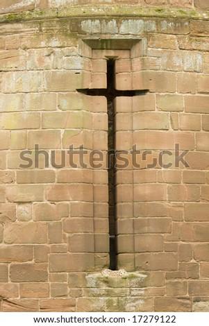 cross shaped window in ruins of castle