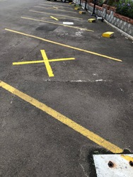 Cross sign of social distancing in parking lot to avoid virus spreading
