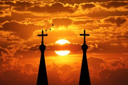 Cross silhouette of steeple lamp with sunset background