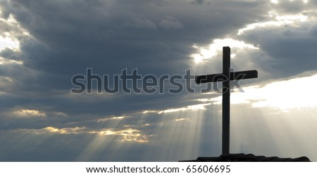 Cross silhouetted against clouds and rays of the sun