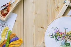 Cross-stitch set : hoop with embroidered flowers pattern, canvas, colorful threads, color palette. Wooden background. Hobby, handmade home decor concept. DIY. Copy space