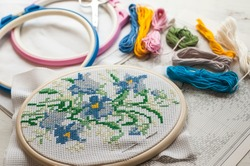 Cross-stitch set : hoop with embroidered flowers pattern, scissors, canvas and colorful yarn. Selective focus. Freelance, hobby, handmade home decor concept