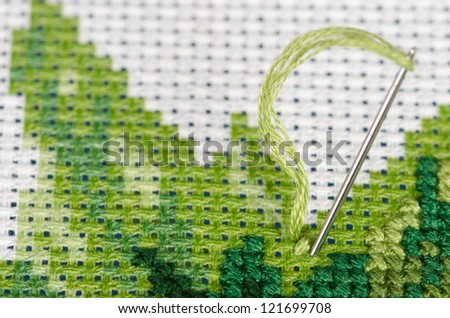 Cross stitching with a needle very closeup
