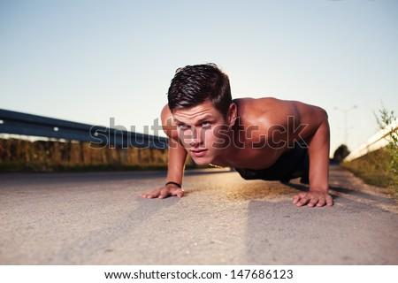 cross-training during sunset. Young man doing push ups.