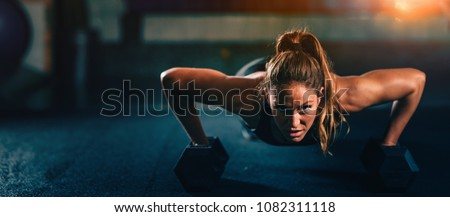 Cross training. Young woman exercising with dumbbells