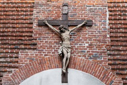 Cross with crucifixion of Jesus on the facade of the ancient Armenian Catholic cathedral in Lviv, Ukraine. The concept of ancient religious architecture of Eastern Europe.