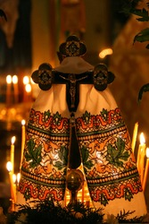 Cross with embroidered towel and burning candles in orthodox church. Concept for religion and prayer.