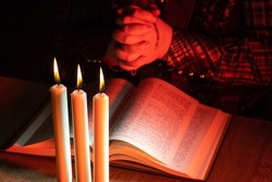 Crossed arms over book. Prayer next to bible. Crossed hands as a symbol of prayer. Praying man reading Catholic Bible. Church candles next to praying hands. Reading a prayer next to church candles