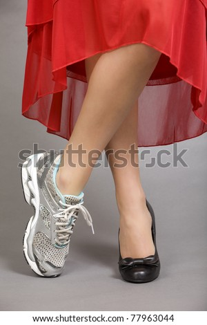 Crossed legs of a beautiful woman wearing and evening gown with one running shoe and one dress shoe